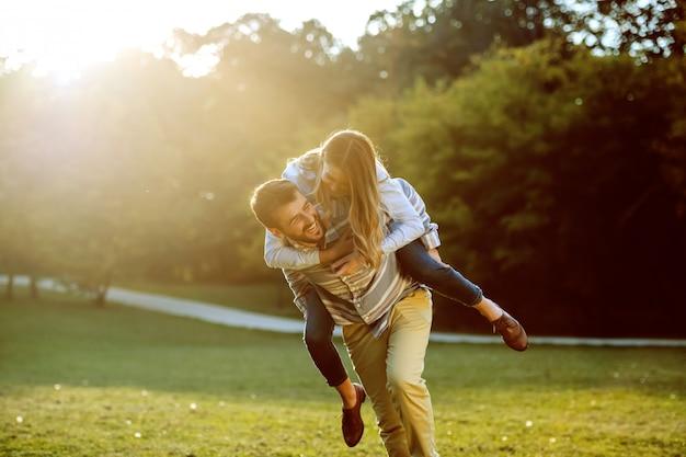 Coppie caucasiche sveglie nell'amore divertendosi sulle spalle e divertendosi in natura.