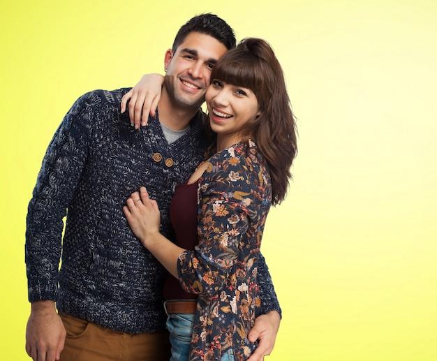 Coppie che abbracciano con uno sfondo giallo