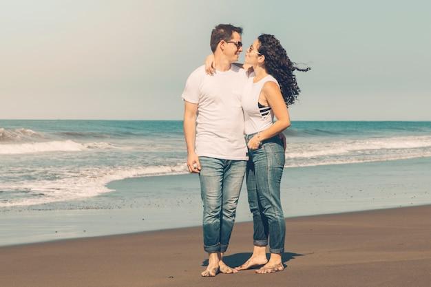 Coppie che abbracciano sulla spiaggia di sabbia