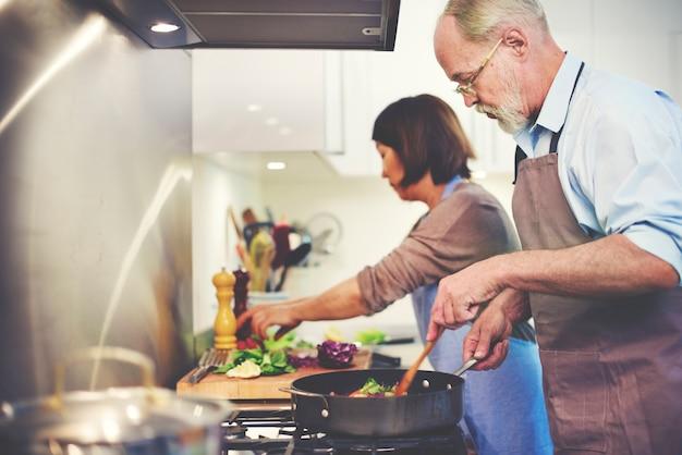Coppie che aiutano cucinando concetto della preparazione