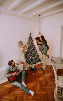 Coppie che appendono le decorazioni di natale sull'albero