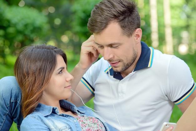 Coppie che ascoltano insieme la musica sul picnic