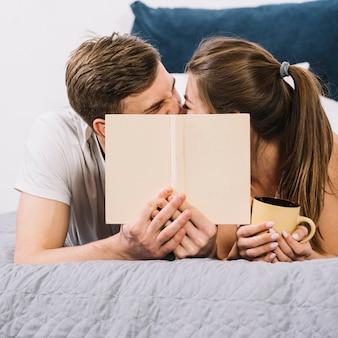 Coppie che baciano i volti della copertura sul letto