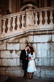 Coppie che baciano in strada che si appoggia sulla parete dell'edificio