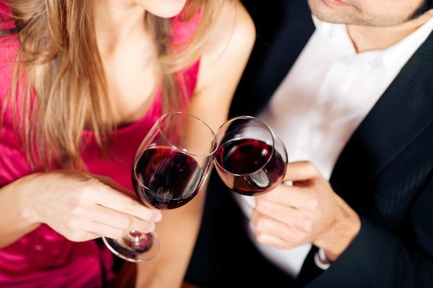 Coppie che bevono i bicchieri tintinnanti del vino rosso