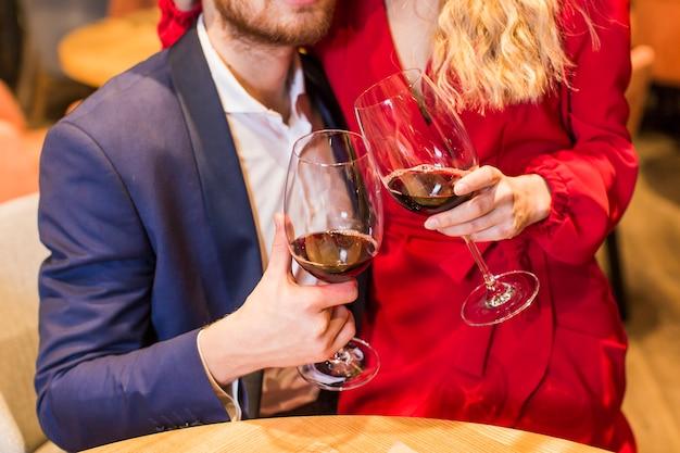 Coppie che clanging i vetri di vino alla tabella