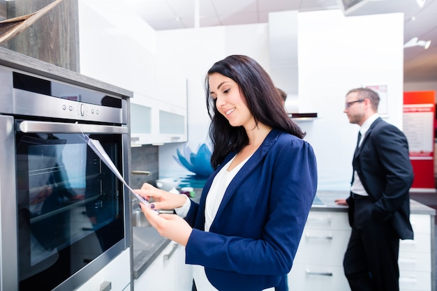 Coppie che comprano cucina domestica in negozio di mobili