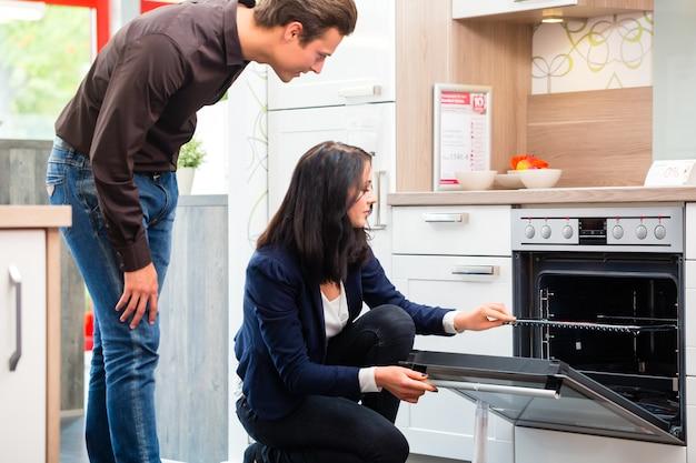 Coppie che comprano cucina domestica in sala d'esposizione