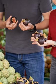 Coppie che comprano intorno alle melanzane