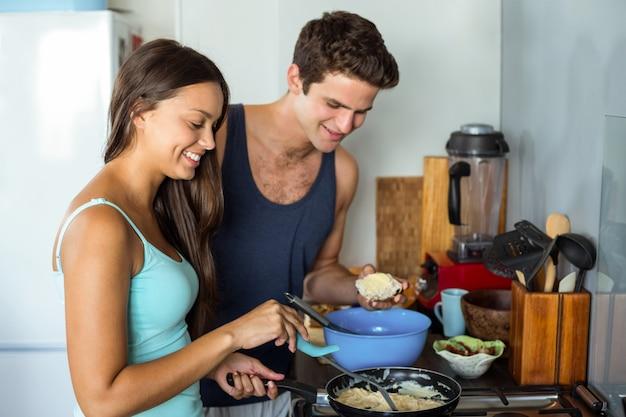 Coppie che cucinano alimento in cucina a casa