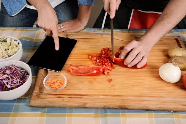 Coppie che cucinano cena facendo uso di una compressa digitale e sorridenti nella cucina