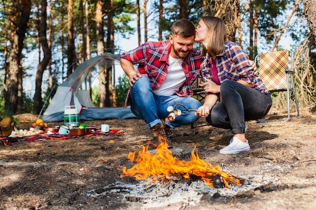 Coppie che cucinano marshmellow al fuoco all'aperto