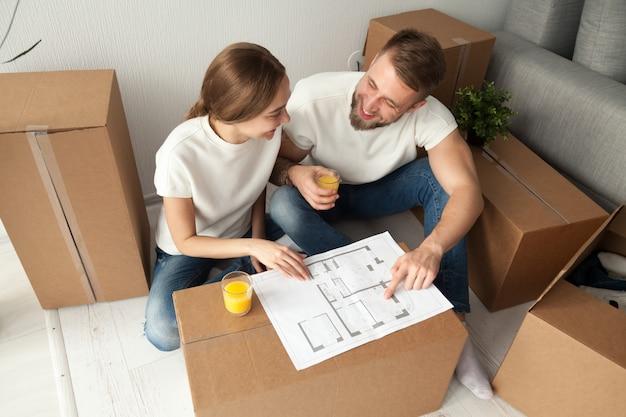 Coppie che discutono pianta della casa che si siede sul pavimento con le scatole commoventi