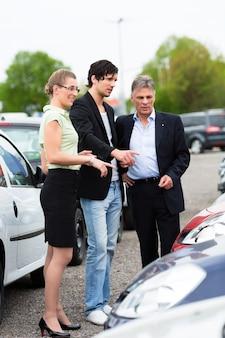 Coppie che esaminano automobile sull'iarda del commerciante