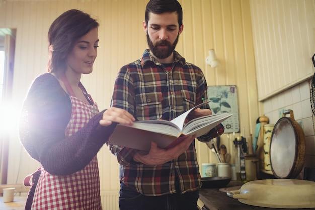 Coppie che esaminano il libro di ricette in cucina