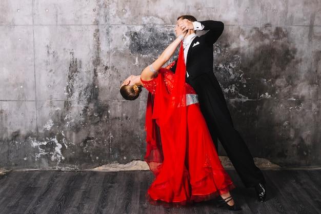 Coppie che eseguono ballo vicino alla parete grigia