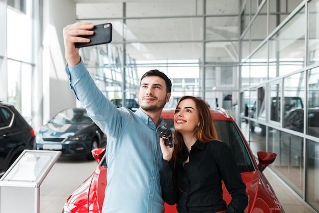 Coppie che fanno selfie in un concessionario auto