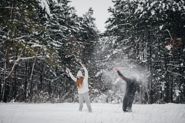 Coppie che giocano con la neve nella foresta