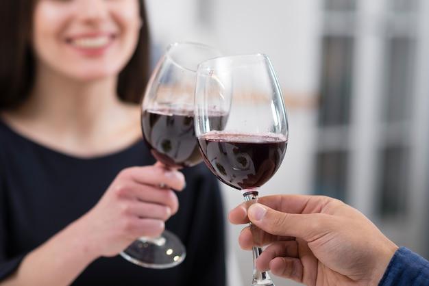 Coppie che incoraggiano con il primo piano dei bicchieri di vino
