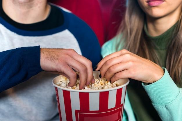 Coppie che mangiano popcorn nel cinema