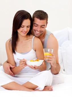 Coppie che mangiano prima colazione nutritiva a letto