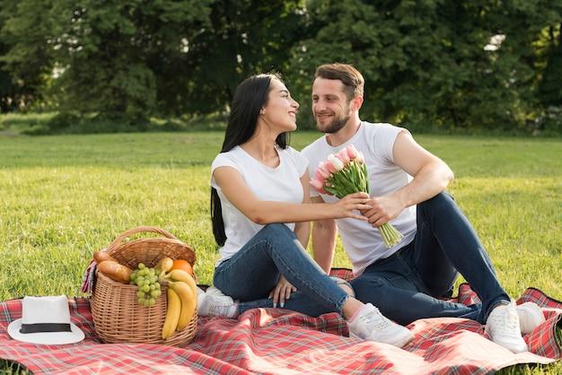 Coppie che posano su una coperta da picnic
