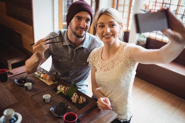 Coppie che prendono selfie mentre mangiano i sushi