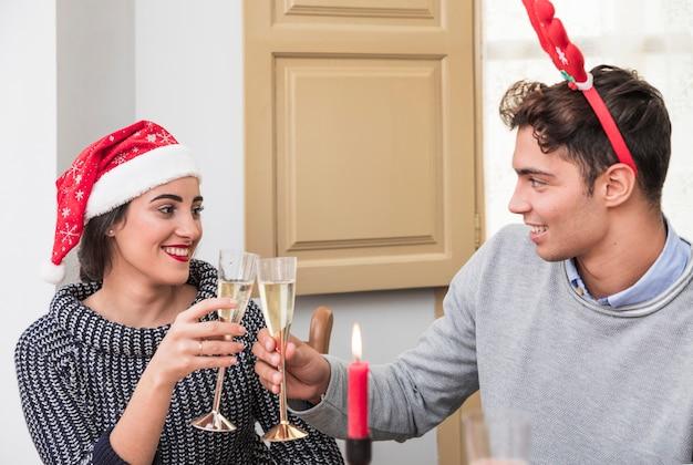 Coppie che risuonano i vetri del champagne alla tavola festiva