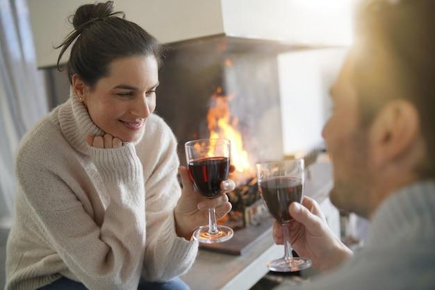 Coppie che si rilassano accanto al fuoco gustando un bicchiere di vino rosso