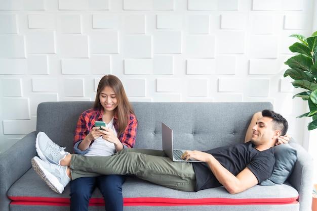 Coppie che si rilassano sul divano a casa. usando mobile e laptop per giocare, lavorare e connettersi a peop
