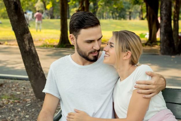 Coppie che si siedono e che abbracciano nel parco.
