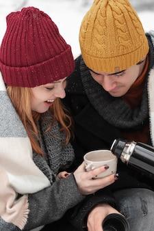 Coppie che si siedono e che bevono il primo piano delle bevande calde