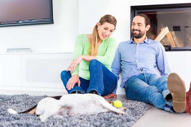 Coppie che si siedono nel pavimento del salone che gioca con il cane