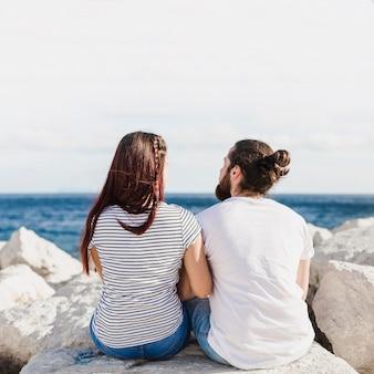 Coppie che si siedono sulle rocce al mare