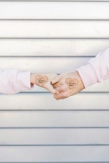 Coppie che si tengono per mano con i simboli decorativi di cuore