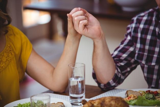 Coppie che si tengono per mano mentre sedendosi al tavolo da pranzo
