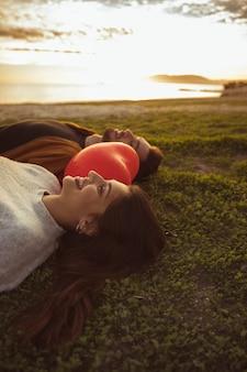 Coppie che si trovano sull'erba con palloncino cuore rosso