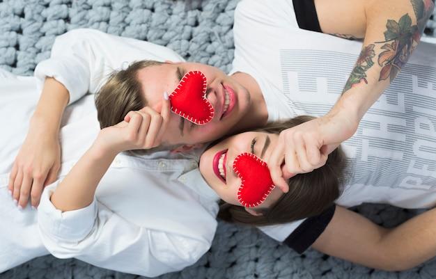 Coppie che tengono i cuori rossi del giocattolo ai fronti