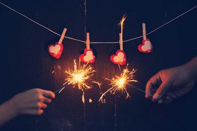 Coppie che tengono le stelle filanti brucianti con il concetto del fondo del biglietto di s. valentino.