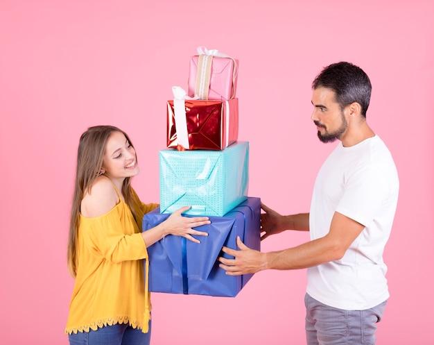 Coppie che tengono pila di scatole regalo colorate su sfondo rosa