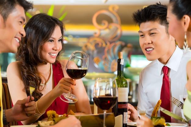 Coppie cinesi che tostano con vino in ristorante