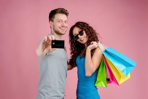 Coppie con i sacchetti della spesa e la carta di credito isolata