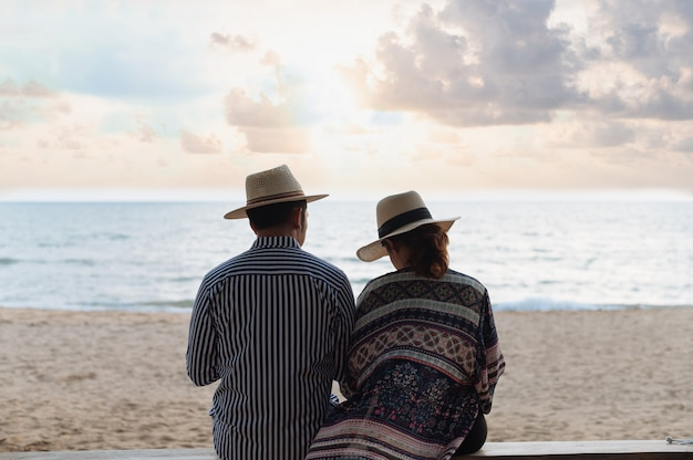 Coppie con il cappello di paglia che si siede sulla spiaggia quando il tramonto