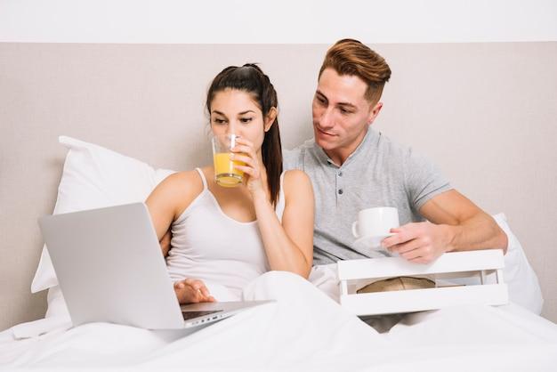 Coppie con il computer portatile facendo colazione a letto
