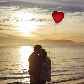 Coppie con l'aerostato del cuore che abbraccia sulla riva di mare nella sera