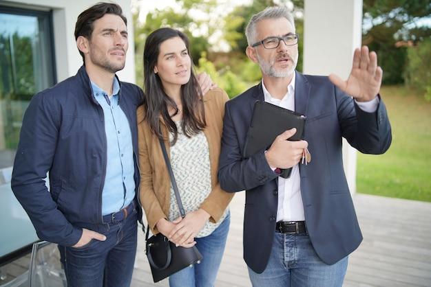 Coppie con l'agente immobiliare che visita casa moderna