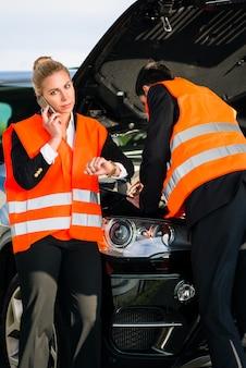 Coppie con la ripartizione dell'automobile che chiama la società di rimorchio