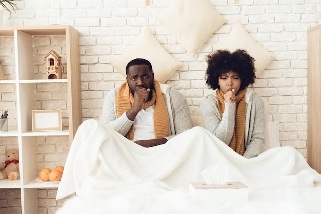 Coppie con la tosse che si siede sul letto a casa.