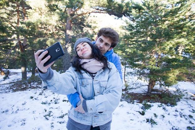Coppie degli amanti felici che godono nella neve che fa un selfie.
