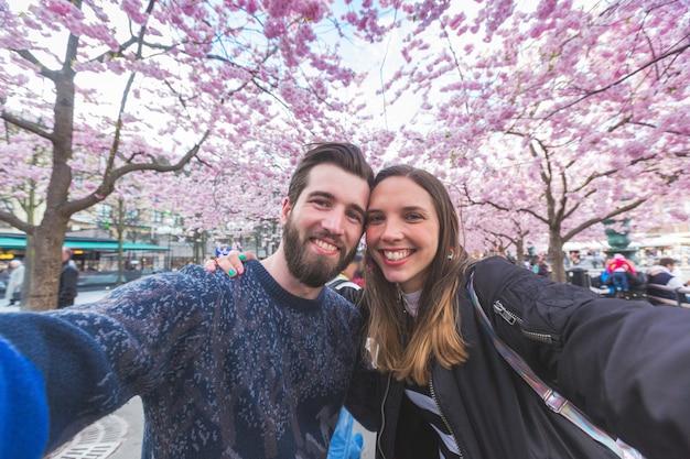 Coppie dei pantaloni a vita bassa che prendono un selfie a stoccolma con i fiori di ciliegia